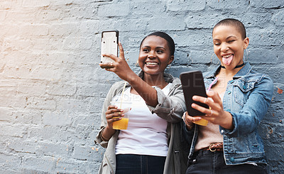 Buy stock photo Shot of two young women standing beside a building smiling and taking selfies while holding their cool drinks