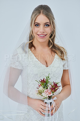 Buy stock photo Studio portrait of a beautiful young bride holding a bunch of flowers on her wedding day against a gray background