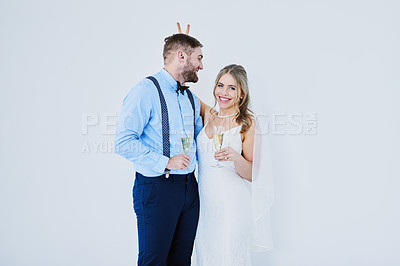 Buy stock photo Studio portrait of a happy young couple sharing a playful moment on their wedding day against a gray background