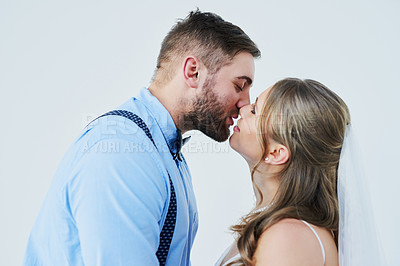Buy stock photo Studio shot of a happy young couple kissing on their wedding day against a gray background