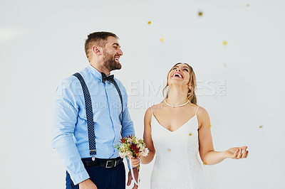 Buy stock photo Studio shot of a happy young couple surrounded with confetti on their wedding day against a gray background