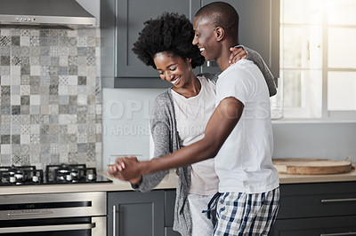 Buy stock photo Shot of a happy young couple dancing together in the kitchen at home