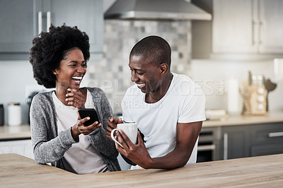 Buy stock photo Shot of a happy young couple using a mobile phone together over coffee at home