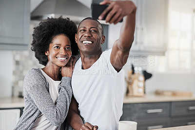 Buy stock photo Shot of a happy young couple taking selfies together at home