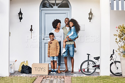 Buy stock photo Shot of a happy family standing in front of their new home