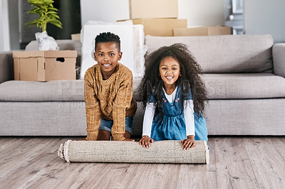 Buy stock photo Portrait of two adorable little siblings rolling out a carpet together in their new home