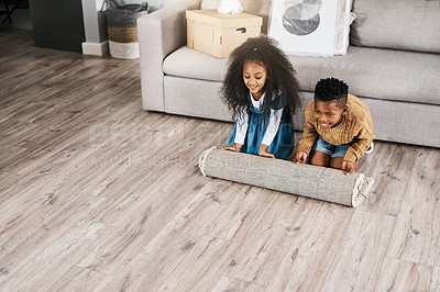 Buy stock photo Shot of two adorable little siblings rolling out a carpet together in the new home