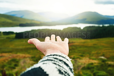 Buy stock photo Cropped shot of an unrecognizable woman extending her arm against a nature background