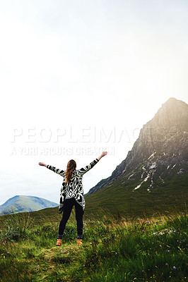 Buy stock photo Rearview shot of a young woman standing with her arms outstretched while exploring nature