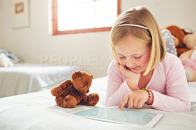 Buy stock photo Shot of an adorable little girl using a digital tablet at home