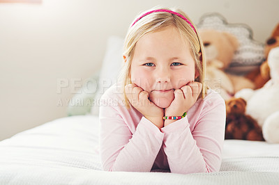 Buy stock photo Portrait of an adorable little girl relaxing on a bed at home