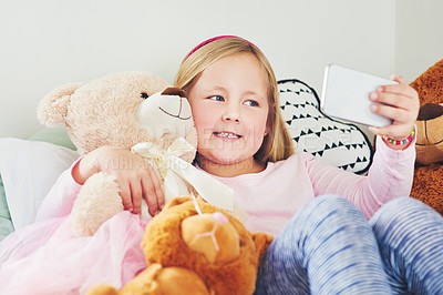 Buy stock photo Shot of an adorable little girl taking selfies with her teddy bears at home
