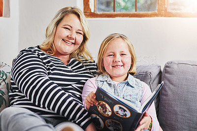 Buy stock photo Portrait of a little girl reading a book with her mother at home