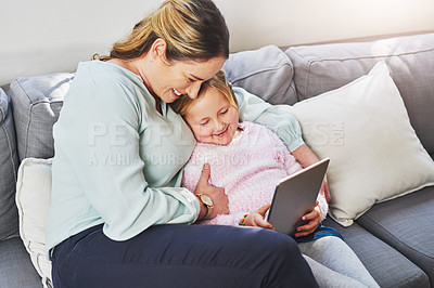 Buy stock photo Shot of a little girl using a digital tablet with her mother at home