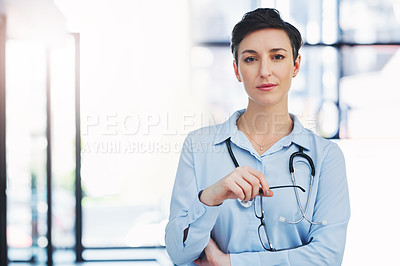 Buy stock photo Cropped portrait of an attractive young female doctor standing in the hospital