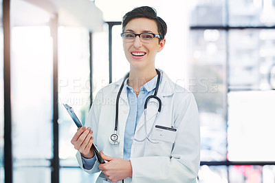 Buy stock photo Cropped portrait of an attractive young female doctor standing with her clipboard in the hospital