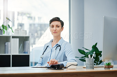 Buy stock photo Cropped portrait of an attractive young female doctor sitting at her desk in the hospital