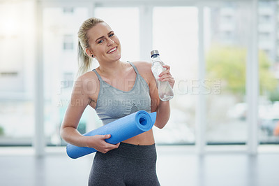 Buy stock photo Portrait of a sporty young woman holding a yoga mat and a water bottle in a studio