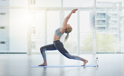 Buy stock photo Shot of a young woman practicing yoga in a studio