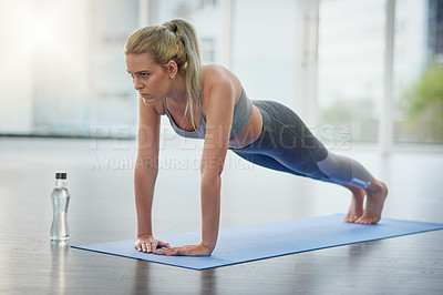 Buy stock photo Shot of a sporty woman practicing yoga at home