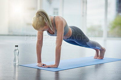 Buy stock photo Shot of a sporty young woman exercising in a studio