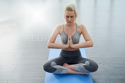 Buy stock photo Shot of a sporty young woman meditating in a studio