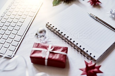 Buy stock photo Shot of a Christmas gift and notebook on a desk in an office