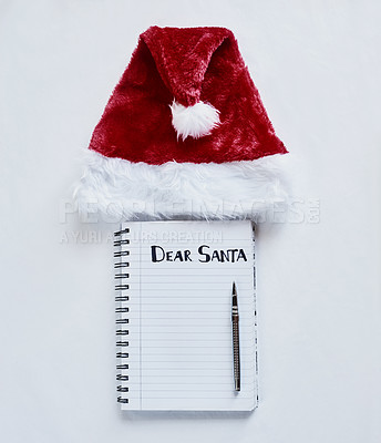 "Buy stock photo Shot of a Santa hat and a notebook with the words, ""Dear Santa"" on it"