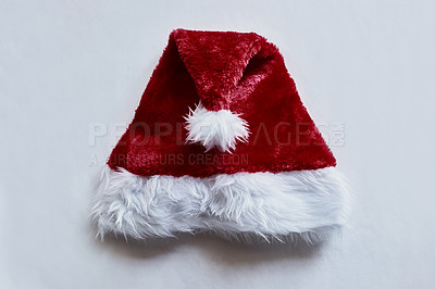 Buy stock photo Shot of a red Santa hat lying on a table