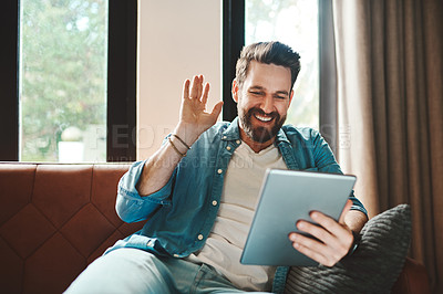 Buy stock photo Cropped shot of a handsome young man on a video call using his tablet while chilling on the sofa at home