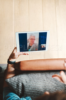 Buy stock photo Cropped shot of an unrecognizable man on a video call using his tablet while chilling on the sofa at home