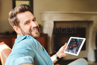 Buy stock photo Cropped shot of handsome young man using a tablet while chilling on the sofa at home