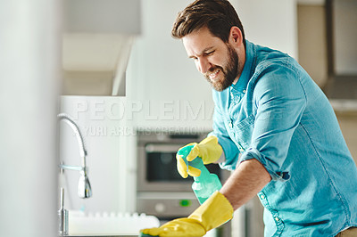 Buy stock photo Cropped shot of a handsome young man cleaning at home