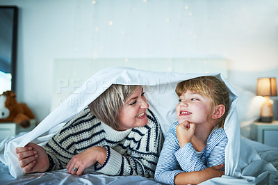 Buy stock photo Shot of an adorable little girl playing with her mother under a blanket at bedtime