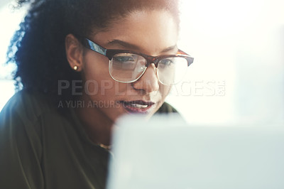 Buy stock photo Shot of a young businesswoman busy working on her laptop in a modern office