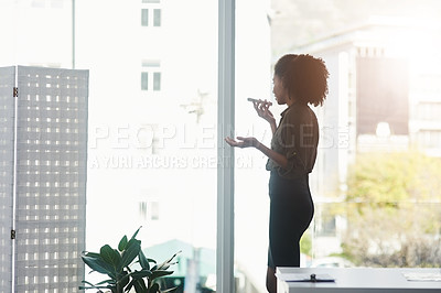 Buy stock photo Shot of a young businesswoman standing in her office and busy talking on a smartphone