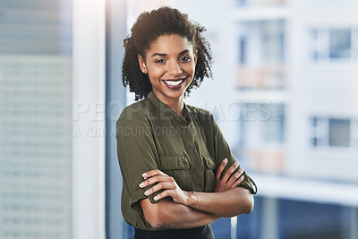 Buy stock photo Portrait of a confident young businesswoman standing in her office with her arms folded