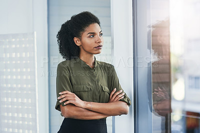 Buy stock photo Shot of a young businesswoman looking out of a window in her office