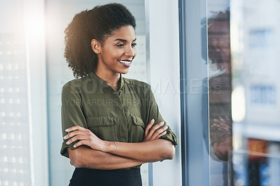 Buy stock photo Shot of a confident young businesswoman looking out of a window in her office