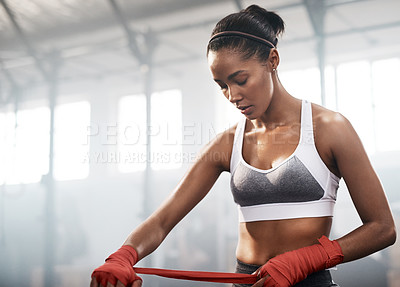 Buy stock photo Cropped shot of an attractive and athletic young woman strapping her wrists while sitting in the gym