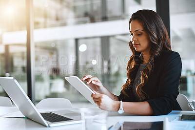 Buy stock photo Cropped shot of an attractive young businesswoman working on her tablet in the office