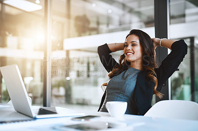 Buy stock photo Cropped shot of an attractive young businesswoman sitting with her hands behind her head at her desk in the office