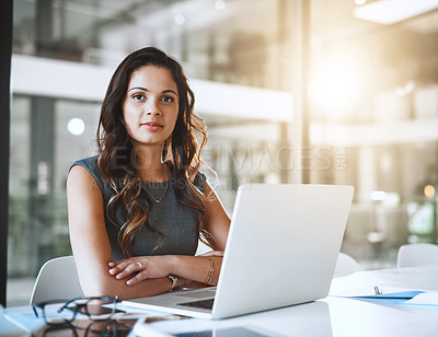 Buy stock photo Cropped portrait of an attractive young businesswoman working on her laptop in the office