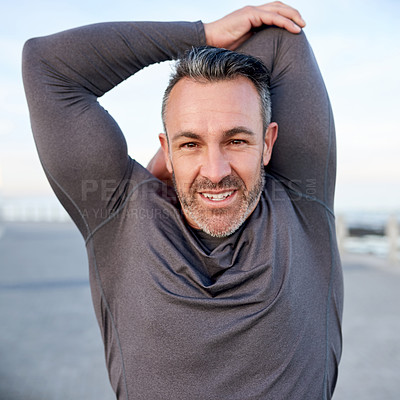 Buy stock photo Shot of a mature man warming up before his run