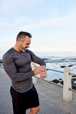 Buy stock photo Shot of a man checking his wristwatch while exercising outdoors