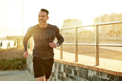 Buy stock photo Shot of a mature man running on the promenade as part of his exercise routine