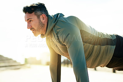 Buy stock photo Shot of a mature man doing push-ups as part of his exercise routine