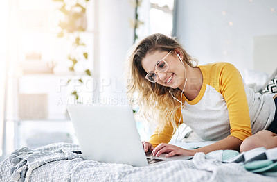 Buy stock photo Cropped shot of an attractive young woman blogging and listening to music while sitting on her bed at home