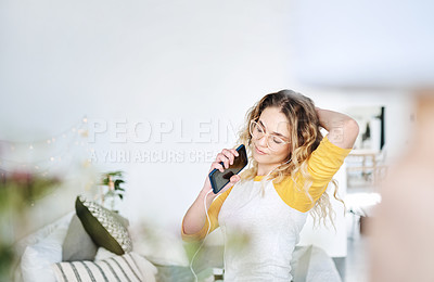 Buy stock photo Cropped shot of an attractive young woman singing and dancing in her bedroom at home