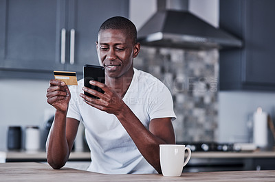 Buy stock photo Shot of a young man using a mobile phone and credit card at home